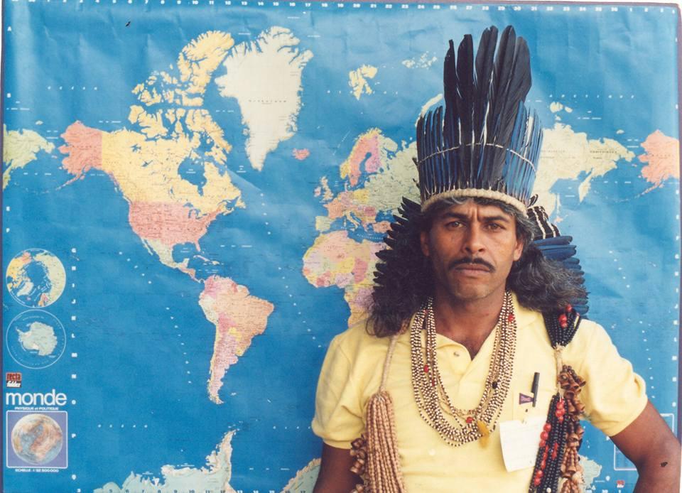 Fotografia de Cacique Xikão Xukuru de Pernambuco, no fundo o mapa do mundo.