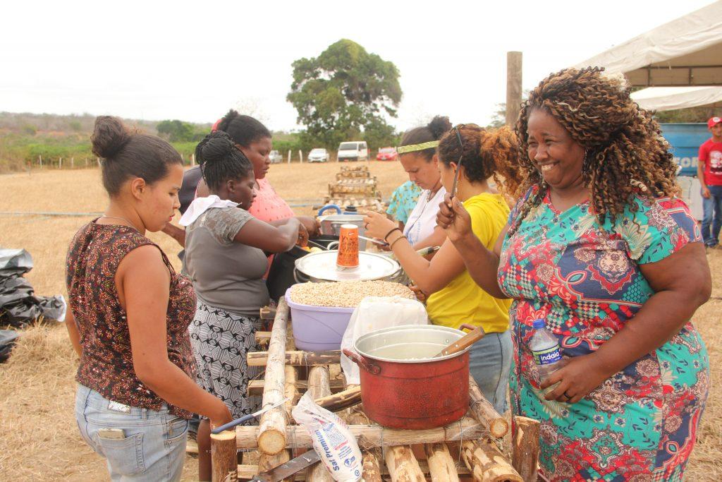 Momento do almoço em uma das cozinhas comunitárias, à esquerda Liderança Mara do MPA servindo a comida.